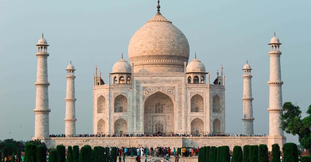 A group of people standing in front of Taj Mahal